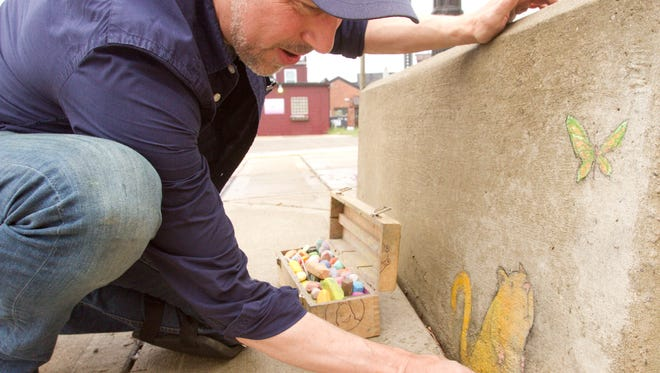 Sidewalk artist David Zinn touches up one of his recently completed works in downtown Brighton, working with a variety of types of chalk ranging from Crayola brand to a specific charcoal stick designed for artists which is optimal for shading.