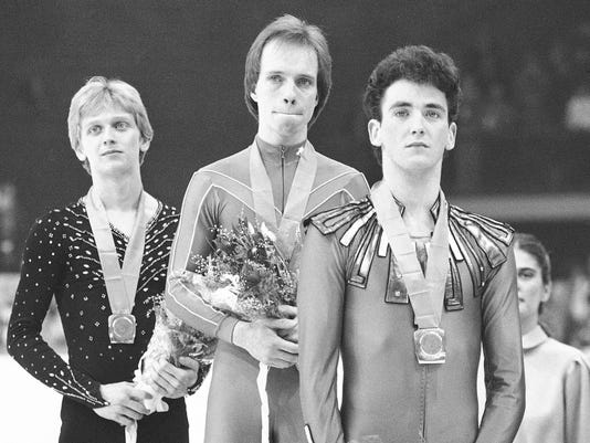 FILE - In this Feb. 16, 1984, file photo, Scott Hamilton, center, of Denver, Colo, has tears in his eyes as he is flanked by Josef Sabovtchik, left, of Czechoslovakia, and Canada's Brian Orser on the podium, after they were awarded gold, bronze and silver medals respectively in the men's free skating competition in Sarajevo. Orser's resume as a coach is as sterling as it was as a competitor in the 1980s, when he won two Olympic silver medals. (AP Photo/File)