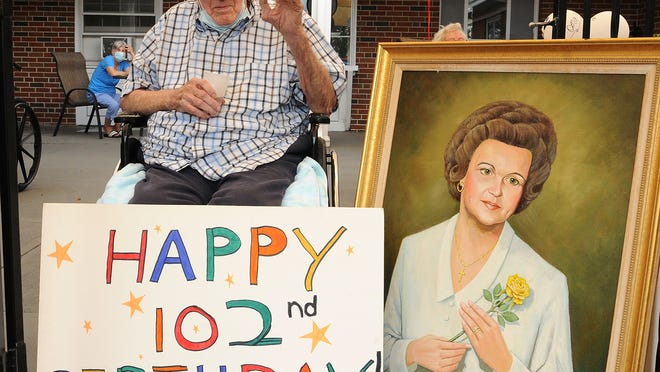 Alfred Bianchi waves to family and friends celebrating his 102nd birthday at the Homestead Hall nursing home in Worcester on Monday. Bianchi painted the portrait of his late wife, Helen.