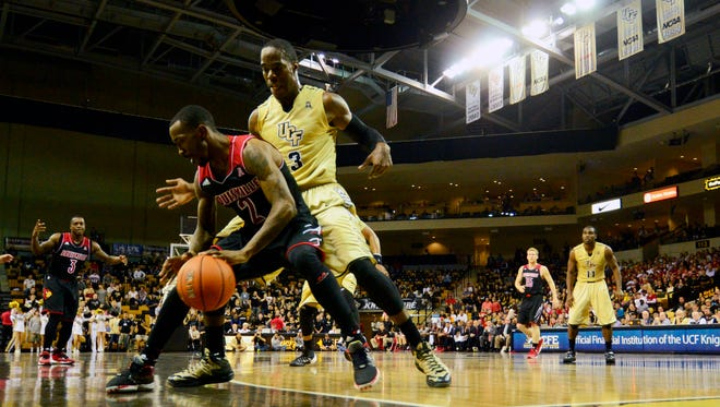 Louisville Cardinals guard Russ Smith backs in on Central Florida Knights guard Isaiah Sykes.