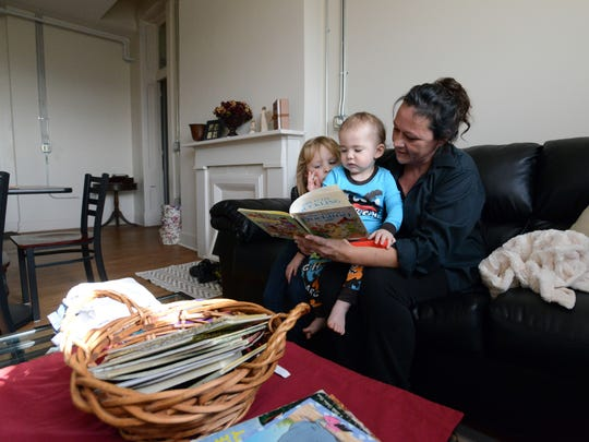 Jean Doss reads to her grandchildren, Luna Hastings, 4, left, and Jaxson Neff, 1, at her new apartment at the Rutherford House in Lancaster.