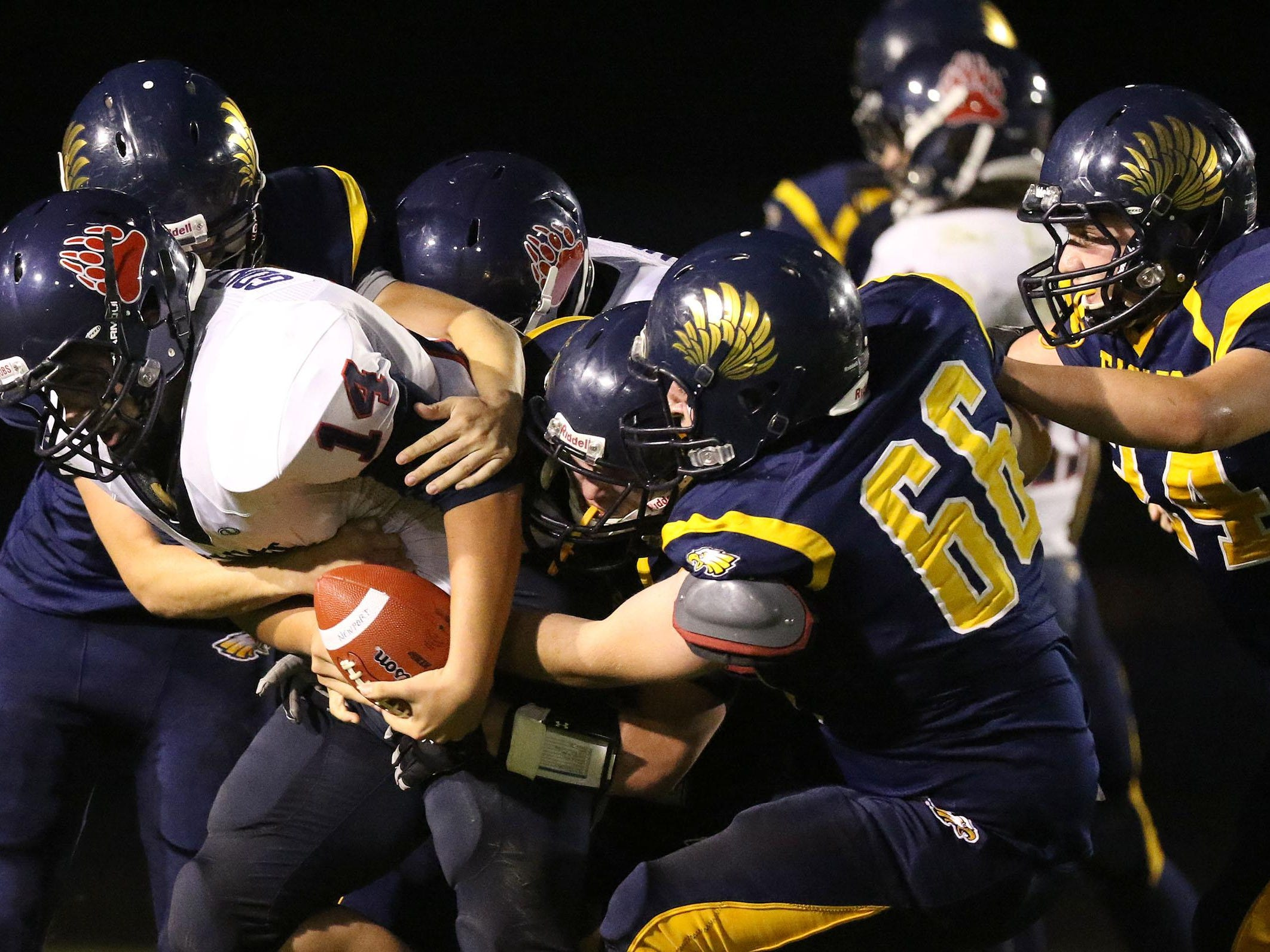 Newport's Austin Gonzales (14) is brought down by Stayton defenders during their game on Friday, Sept. 25, 2015, in Stayton, Ore.