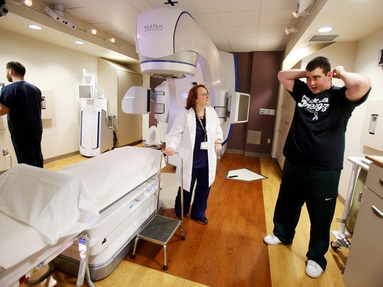 Kathleen M. Faber, center, waits for patient Ryan Lee Smigiel, 21, right, of Essexville, to get ready to have his daily radiation therapy for a rare brain tumor on Dec. 16 at Henry Ford.