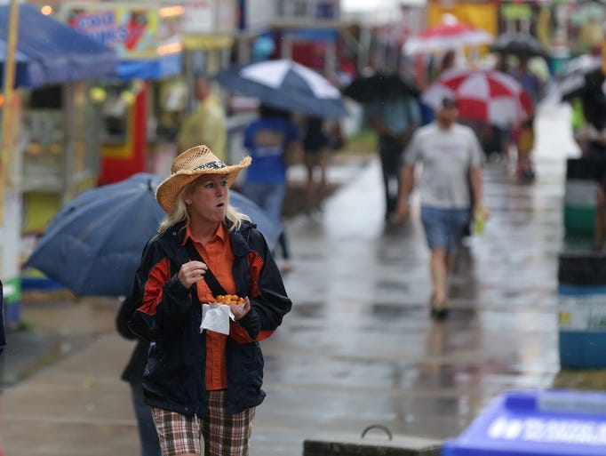 Fairgoers seek refuge from the rain under umbrellas during the Iowa State Fair on Friday, Aug. 15, 2014, in Des Moines.