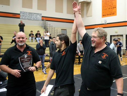 Central Kitsap wrestling coach Mike Harter (right) was honored for his 15 years of coaching during Saturday's Matman Classic at Central Kitsap. Harter is retiring at the end of the year. Joining Harter were assistant coaches Marty Neyman (left) and Joey Troyer (center).