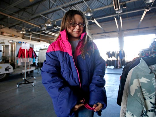 Juliana Chairez, 11, of Farmington, tries on a winter coat during the Coats for Kids distribution event on Saturday at Farmington Fire Station No. 6.