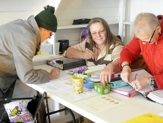 Volunteers Casey Butcher (center) and Debbie Kusmerz