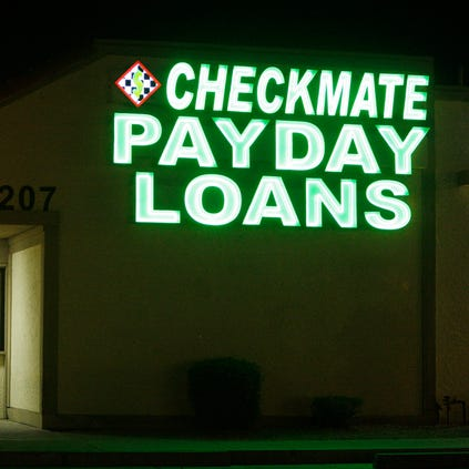 Neon signs illuminate a payday loan business in Phoenix on Tuesday, April 6, 2010, one of 650 operating in the state with some open 24-hours a day.