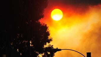 Smoke from the Scoggins Creek fire north of Hagg Lake clouds the sun from downtown Forest Grove, Ore., on Friday, Sept. 19, 2014.