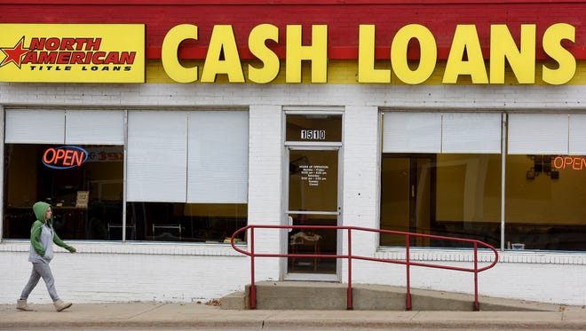 A pedestrian walks past the North American Title Loans agency off of E. 10th St. in Sioux Falls  on Wed., Oct. 26, 2016.