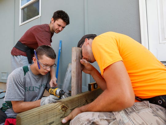 SPS student Elijah Stevens gets help from Eric Wandra, top left, and site leader Steven San Paolo while building a deck at the Habitat for Humanity site at Legacy Court on Friday, June 15, 2018.