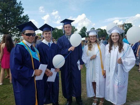 Phillip Griffor, Garrett James, Brendan Thorpe, Gabby Satryb, and Ginger Jones release balloons after their graduation ceremony to honor their deceased parents.