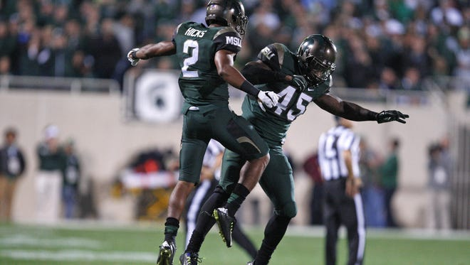 Michigan State cornerback Darian Hicks (2) and linebacker Darien Harris (45) celebrate after the Spartans got a fourth-down stop against Oregon earlier this month.