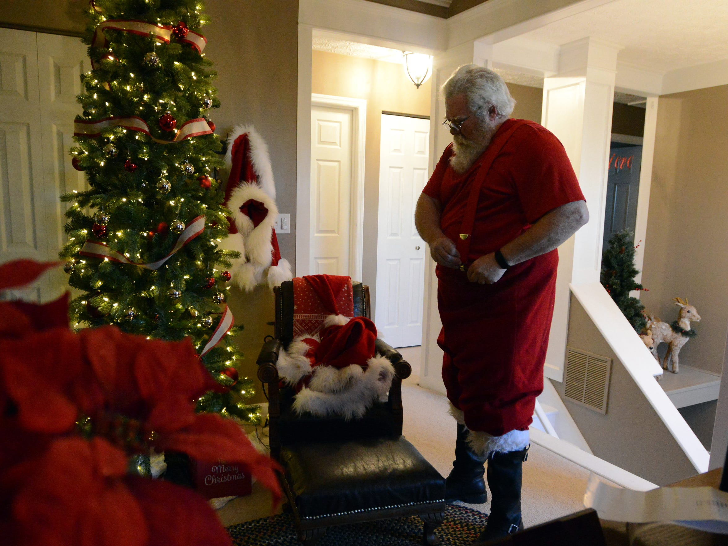 Tim Etienne puts on his suspenders as he dresses in his traditional Santa Claus suit Friday evening, Dec. 1, 2017, at his home in Canal Winchester.