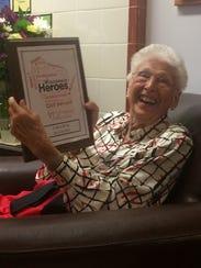 Carol Bush shows family the Wisconsin Heroes Award
