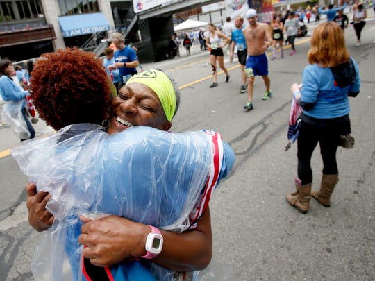 Diana Kinard of Augusta, Ga., gets a hug from friend and marathon volunteer Kerlyne Pinkins, who was at the finish line handing out medals at the 40th Detroit Free Press/Chemical Bank Marathon in Detroit on Sunday, Oct 15, 2017. Kinard ran the marathon and finished with a time of 4:40:50.