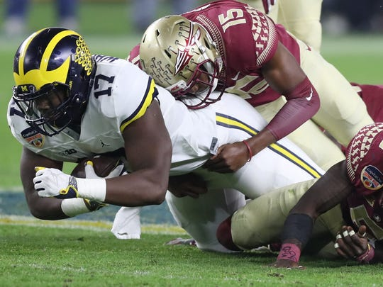 Michigan tight end Tyrine Wheatley is tackled by Florida
