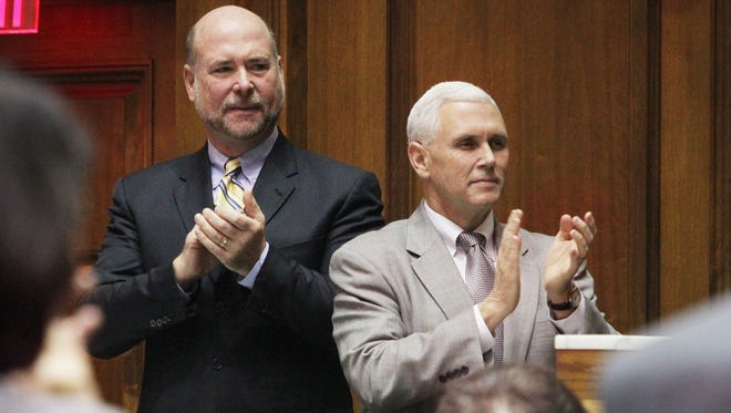 Indiana Speaker of the House Brian Bosma, R-Indianapolis (left) and Gov. Mike Pence applaud Supreme Court Chief Justice Brent Dickson as he prepares to deliver the State of the Judiciary address to legislators in January 2014.