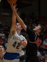 Castle's Zach Messinger (42) and Harrison's Rilee Epley go for a rebound during their SIAC semifinal at Castle.