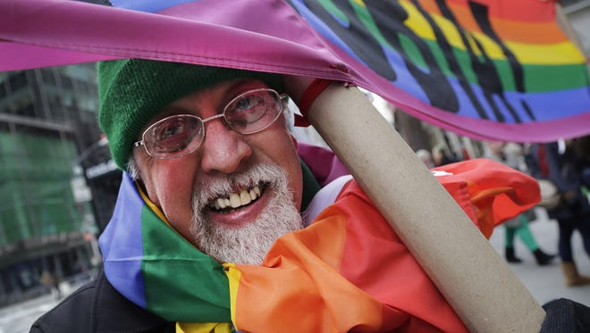 """Artist Gilbert Baker, designer of the Rainbow Flag, is draped with the flag while holding a banner that reads """"Boycott Homophobia"""" before the start of the St. Patrick's Day parade, Monday, March 17, 2014 in New York. The city's  parade stepped off Monday without Mayor Bill de Blasio marching along with the crowds of kilted Irish-Americans and bagpipers amid a dispute over whether participants can carry pro-gay signs. (AP Photo/Mark Lennihan)"""