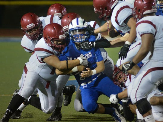 Fillmore quarterback Hector Sanchez is tackled by a swarm of Santa Paula defenders during Friday night's game at Fillmore High.