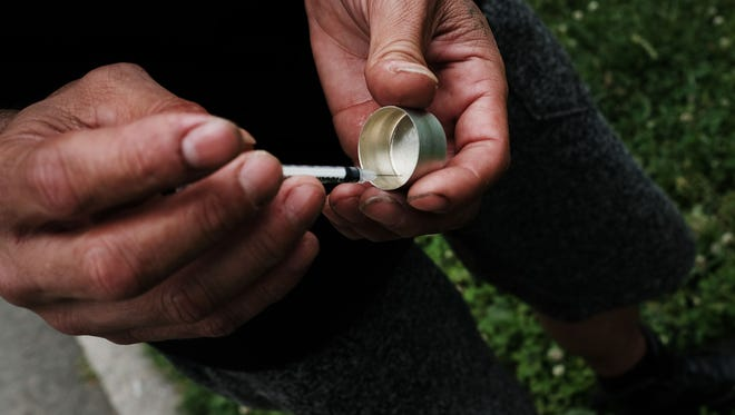 A man shoots heroin in a park in the South Bronx.