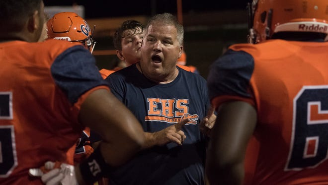 Escambia High School head football coach Mike Bennett instructs his players in between quarters of the preseason game against Catholic High School in Pensacola on Friday.