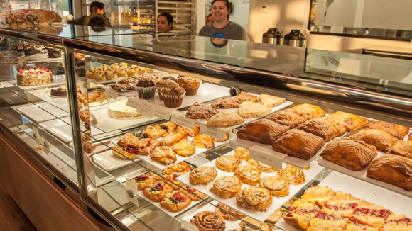 ZuHuase employees tend to the front counter filled with a wide selection of pastry treats.