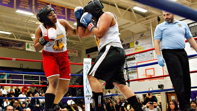 A'Nyah Wray, 14, left, of North York Borough, fights Genesis Orbe DeJesus, 15, of Reading, in a bout match during the Frank Cariello's 2018 Pennsylvania Golden Gloves Tournament at Lancaster Catholic High School in Lancaster, Saturday, March 3, 2018. Wray would win the match by unanimous decision. Dawn J. Sagert photo