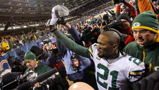 Packers cornerback Charles Woodson holds up an NFC Championship cap after Green Bay beat the Chicago Bears, on Jan. 23, 2011.