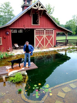 Wade Shealy stands with his dog Hampton at his Franklin farm, called Lucky Dog Farm, where he created a swimming pool that looks like a pond. Shealy is the founder of 3rd Home, which helps those with high-end second homes share with others.