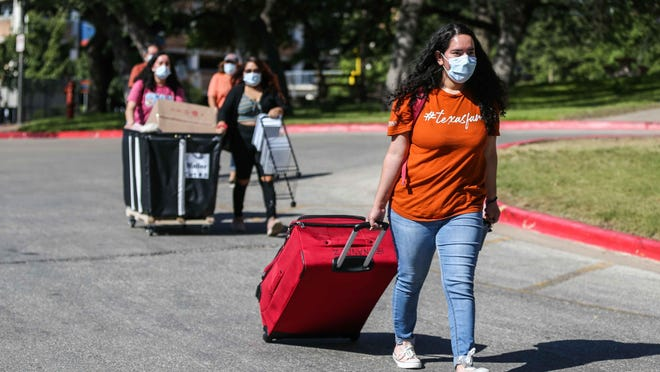 Alyssa Hernandez carries a suitcase as her family helps her move into the San Jacinto Residence Hall at the University of Texas on Thursday. UT's fall semester begins Wednesday. [