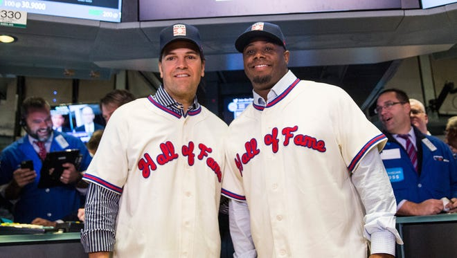 Mike Piazza (L) and Ken Griffey Jr. pose for a photo after ringing the opening bell at the New York Stock Exchange.