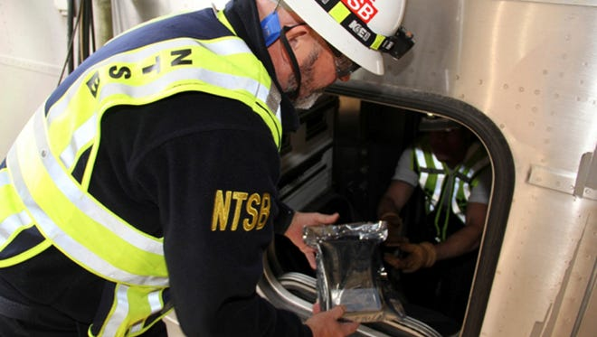 James Southworth, Investigator-in-Charge for the National Transportation Safety Board's investigation, is handed the lead car's video recorder in an anti-static bag from NTSB investigator Michael Hiller, in Hoboken last month.