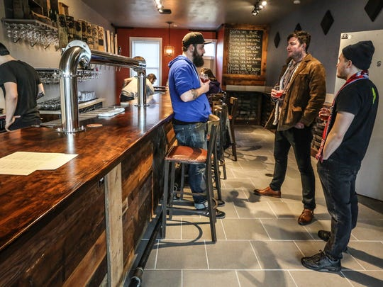 Central State Brewery Co-Founder and Head Brewer, Josh Hambright, center left, chats with Milktooth's Nate Atkins, far right, and Jonathan Brooks, center right, during the soft opening of CSB's Koelschip Tap Room. The Tap Room is located at 2505 Delaware St. Indianapolis, IN.