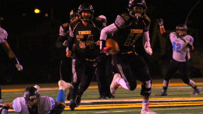 Alamogordo's Chamar Norman races past a fallen Del Norte defender towards the end zone on Friday night at Tiger Stadium during the first round of the Class 5A state playoffs.