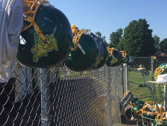 Edgar football helmets line the top of a fence at the