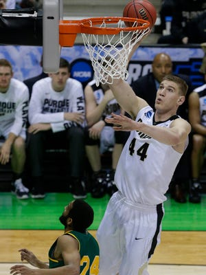 Seven-foot-two-inch Purdue center Isaac Haas scores as Vermont guard Dre Wills during their first-round NCAA Tournament game.