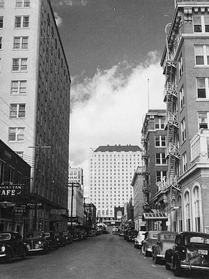 "A 1942 ""Doc"" McGregor photo shows the Jones (Sherman) building on the left, the Nueces Hotel on the right, and the Robert Driscoll Hotel straight ahead on the bluff. This tall-building view of Peoples Street  shows the downtown in its glory days, when the city seemed larger than it was."