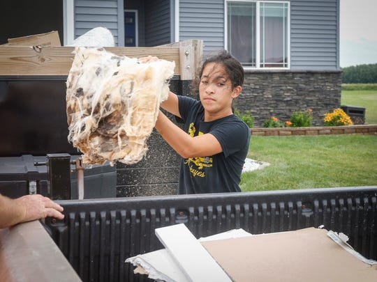 Sydney Bagby, 11, tosses soggy insulation into the