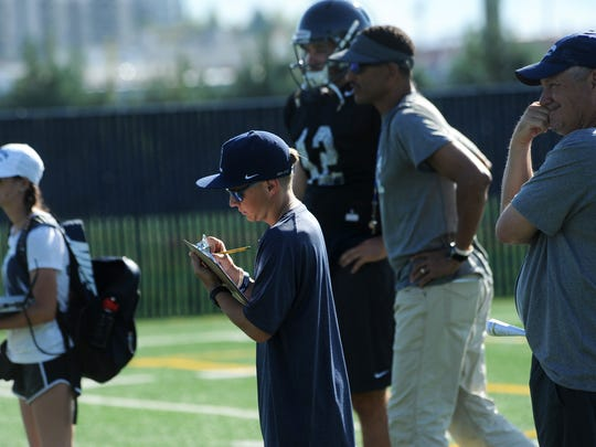 Bailey Johnson, volunteer assistant coach for Nevada football, takes notes during practice this week as head coach Jay Norvell stands in the background.