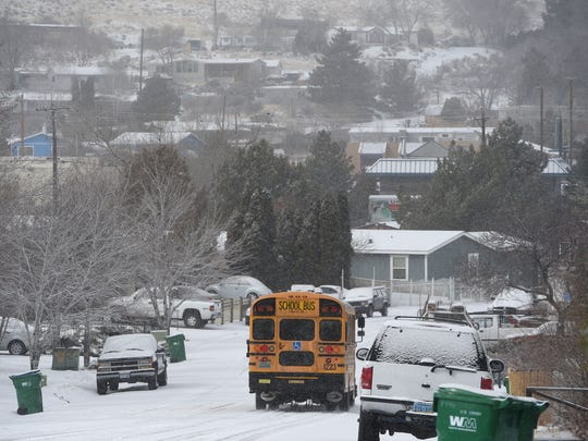 A WCSD bus drives through Sun Valley picking up kids for school on a snowy Thursday morning, Feb. 22, 2018.