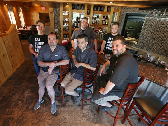 Tim Archetko, owner and head chef, front right, sits