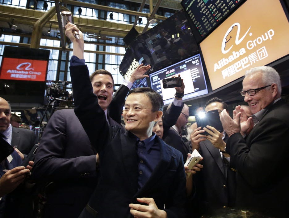Alibaba founder Jack Ma, center, raises a ceremonial mallet before striking a bell during the company's IPO at the New York Stock Exchange on Sept. 19, 2014.