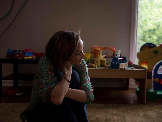 Mara Watts sits on the floor of her living room watching