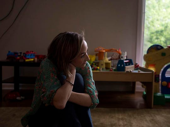 """Mara Watts sits on the floor of her living room watching her four-year-old son Sawyer and her 19-month-old daughter Henley play with their father Adam May 2, 2016. After two months of PPD, Watts was able to pull herself out of that dark place. """"Women feel pressure to be perfect,"""" she said. """"But being honest and vulnerable still means youÕre a strong woman and mother."""""""