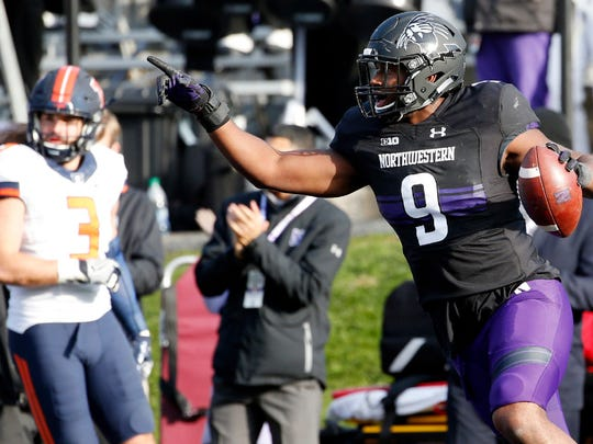 Northwestern slotback Garrett Dickerson points as he celebrates after scoring a touchdown during the second half of an NCAA college football game against Illinois in Evanston, Ill., Saturday, Nov. 26, 2016. Northwestern won 42-21.