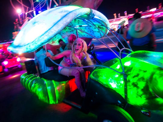 In this Saturday, May 19, 2018, photo, attendees pass by in a small art car during the second day of the Electric Daisy Carnival at the Las Vegas Motor Speedway in Las Vegas. Las Vegas Metro police say 35 people were arrested in the second day of the carnival, including 33 for drug-related felony charges.