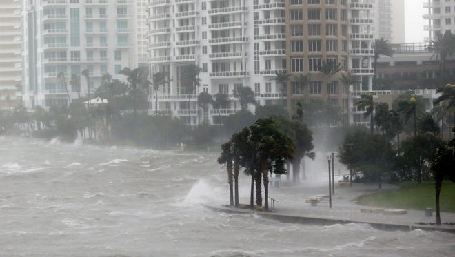 This Sept. 10, 2017 file photo shows waves crashing over a seawall at the mouth of the Miami River from Biscayne Bay, Fla., as storm surge from Hurricane Irma impacts Miami.  Florida's governor and Legislature promised a dizzying array of fixes following the devastation of last year's hurricanes. But heading into Friday, June 1, 2018,  start of a new storm season, the state has enacted only a few changes.