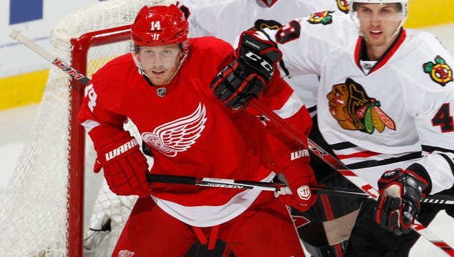 Red Wings forward Gustav Nyquist tries to hold his spot in the crease against the Blackhawks' Viktor Svedberg, right, in the first period of the Wings' win Wednesday at Joe Louis Arena.